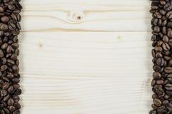 Feld von Kaffeebohnen auf Holztisch Hintergrund Lizenzfreies Stockfoto