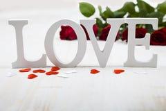 Feld von roten Rosen, Herzen und Wort lieben auf einem hölzernen backgroun Stockfotos