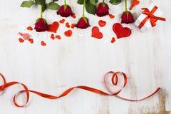Feld von roten Rosen und von Herzen auf einem hölzernen Hintergrund Stockfotografie