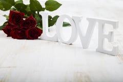 Feld von roten Rosen und Wort lieben auf einem hölzernen Hintergrund Lizenzfreies Stockbild