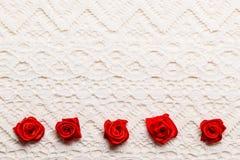 Feld von roten silk Rosen auf Spitze Stockfotografie