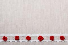 Feld von roten silk Rosen auf Stoff Stockfotos
