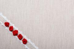 Feld von roten silk Rosen auf Stoff Lizenzfreie Stockbilder