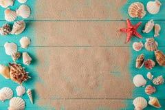 Feld von seashellson auf hölzernem Hintergrund des Sandes Raum für Text Lizenzfreie Stockfotos