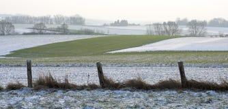 Felder hinter einem schroffen Zaun im Winter Stockbild