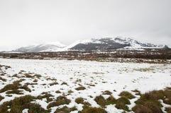 Felder und Berge bedeckt durch den Schnee Stockfotografie