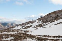 Felder und Berge bedeckt durch den Schnee im Winter Stockbilder