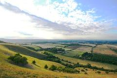Felder und Hügel mit blauem Himmel Lizenzfreie Stockfotos