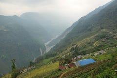 Felder und nebelige Berge in Nepal Stockbild