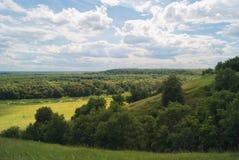 Felder und Wiesen in einem hügeligen Tal unter einem bewölkten Sommerhimmel Lizenzfreies Stockfoto