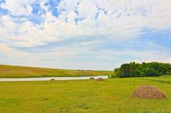 Feldlandschaft mit Fluss und Heu stockfotografie