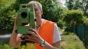 Feldmesser bei der Arbeit, die den Abstand misst stock footage