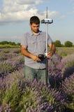 Feldmesser, das sein Instrument auf einem Gebiet des Lavendels justiert Lizenzfreies Stockfoto