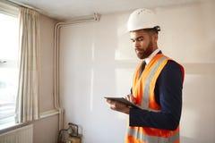 Feldmesser In Hard Hat und hohe Sicht-Jacke mit Digital-Tablet-Durchführungshaus-Inspektion stockfoto