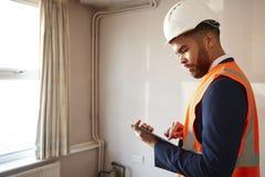 Feldmesser In Hard Hat und hohe Sicht-Jacke mit Digital-Tablet-Durchführungshaus-Inspektion stockbild