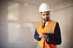 Feldmesser In Hard Hat und hohe Sicht-Jacke mit Digital-Tablet-Durchführungshaus-Inspektion lizenzfreies stockfoto