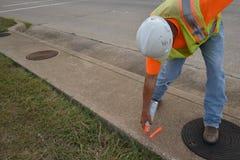 Feldmesser Marking ein Bürgersteig beim Tragen einer Sicherheits-Weste und des Schutzhelms Lizenzfreies Stockbild