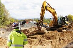 Feldmesser, Planierraupe und Aushubarbeiten Lizenzfreie Stockfotos