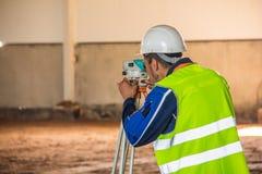 Feldmesserarbeit mit einem Tachymeter, wenn eine Fabrik errichtet wird lizenzfreies stockfoto