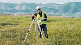 Feldmessermann in der grüner Arbeitskleidung und -sturzhelm justiert die Ausrüstung, produziert Berechnungen und schreibt zum Not stock video