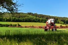 Feldsprühtraktor Landarbeit über einen Bauernhof in der Tschechischen Republik Sprühen gegen Plagen Stockbild
