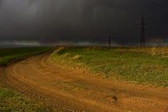 Feldstraße, die in einen Thundercloud geht stockfotografie