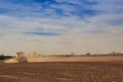 Feldtraktor der Schäfchenwolken des blauen Himmels oben genannter in der großen Staubwolke Stockfotografie