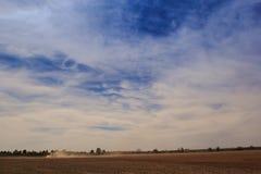 Feldtraktor der Schäfchenwolken des blauen Himmels oben genannter in der großen Staubwolke Lizenzfreies Stockbild