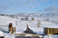 Feldweg, der durch Schnee führt Lizenzfreies Stockbild