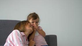 Felice bella famiglia amorevole giovane madre e figlia che ridono seduti sul divano, mamma sorridente con un bambino che si diver stock footage