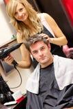 Felice capelli del suo cliente del parrucchiere essiccamento Immagine Stock