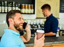 Felice di sentirvi L'imprenditore sicuro sceglie la bevanda in tazza di carta per andare mentre comunichi il cellulare L'uomo par fotografie stock
