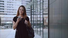 Felice e nelle passeggiate della ragazza di amore attraverso la città con un telefono stock footage