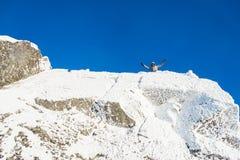 Felice l'alpinista ha scalato il superiore della montagna coperto di ghiaccio e di neve, viandante dell'uomo che celebra il succe Immagini Stock