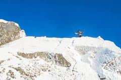 Felice l'alpinista ha scalato il superiore della montagna coperto di ghiaccio e di neve, viandante dell'uomo che celebra il succe Immagine Stock Libera da Diritti