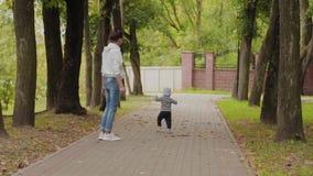 Felice mamma cammina con suo figlio nel parco video d archivio
