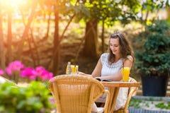 Felice, positivo, bello, la ragazza dell'eleganza che si siede al caffè presenta all'aperto Immagini Stock Libere da Diritti