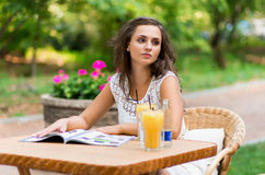 Felice, positivo, bello, la ragazza dell'eleganza che si siede al caffè presenta all'aperto Fotografia Stock