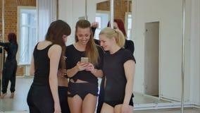 Felice sveglio dancerstaking una rottura dal loro allenamento e rete sociale con un telefono cellulare stock footage