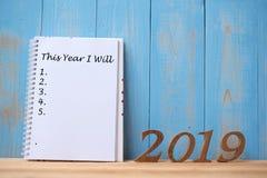 """2019 Felices Año Nuevo con el """" del cuaderno que este año texto del """" y número de madera en espacio de la tabla y de la copia foto de archivo libre de regalías"""