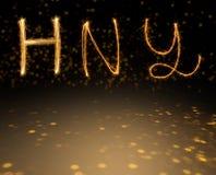 Felices Año Nuevo de los fuegos artificiales de alfabeto de la chispa en fondo del bokeh del oro Imágenes de archivo libres de regalías