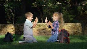 Felices alumnos que juegan al juego que aplaude que se sienta en hierba después de aprender en rotura de la escuela almacen de metraje de vídeo