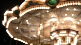 Felices borrosos iluminada van ronda en parque Cruce giratorio brillantemente iluminado que hace girar en parque de atracciones m almacen de metraje de vídeo
