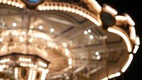 Felices borrosos iluminada van ronda en parque Cruce giratorio brillantemente iluminado que hace girar en parque de atracciones m metrajes