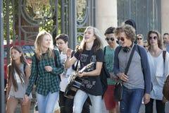 Felices estudiantes con la guitarra que caminan en la calle Imagen de archivo