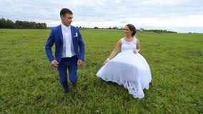 Felices, los recienes casados juntan el funcionamiento en un prado verde almacen de video