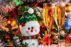 Felices muñeco de nieve y copas con el vino espumoso en el fondo de un árbol de navidad Imágenes de archivo libres de regalías
