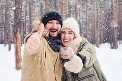 Felices pares que gesticulan y que abrazan en un día nevoso del invierno frío Foto de archivo libre de regalías
