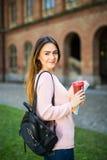 Felici sicuri di laureato di vetro intelligenti astuti dello studente al giardino dell'università con la borsa ed i libri bevono  Fotografie Stock Libere da Diritti