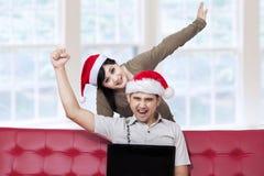 Felicidad de los pares jovenes que hacen compras en línea Imagenes de archivo